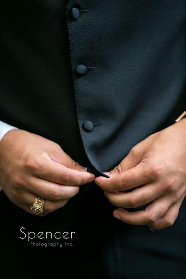 groom buttoning vest before Firestone wedding