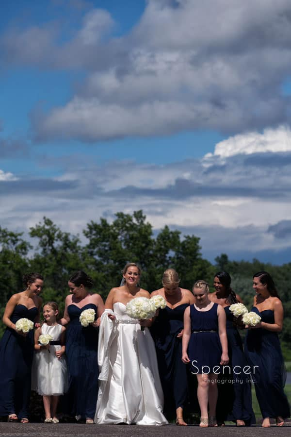 bride walking with bridesmaids on her wedding day at firestone country club