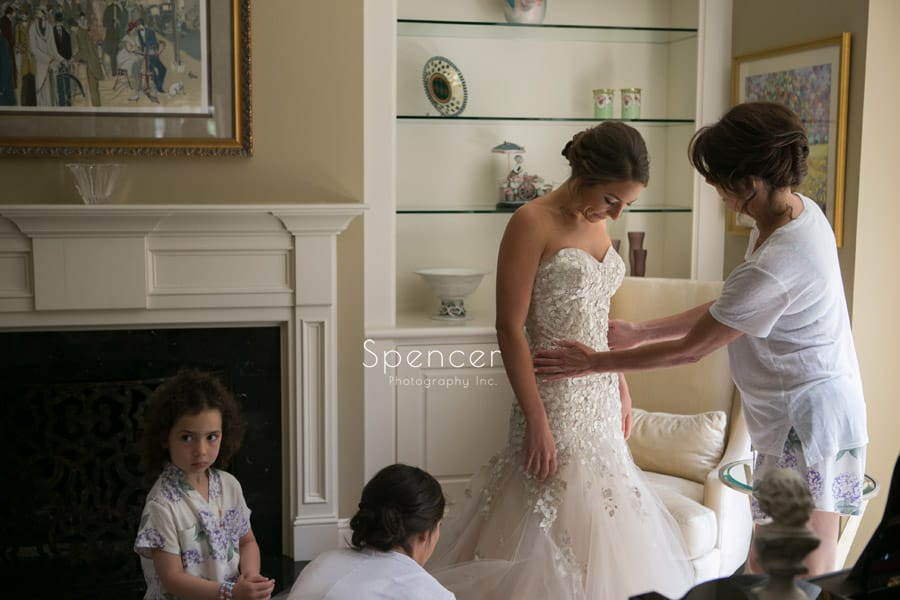 bride putting on her liancarlo wedding dress
