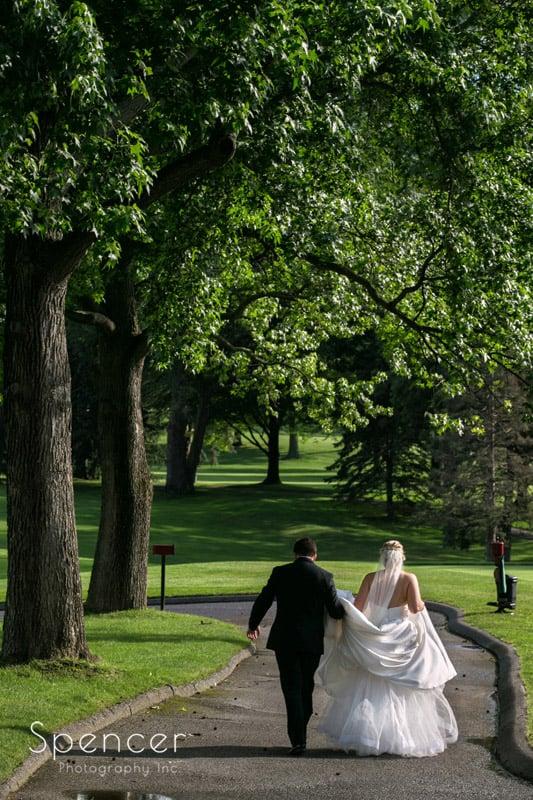 bride and groom walking cart path at Firestone Country Club Wedding Reception