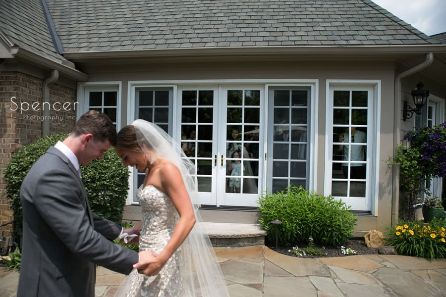 groom looking at brides wedding dress