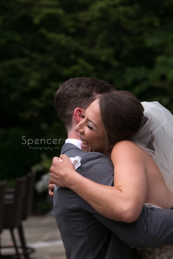 a joyful bride hugs her groom