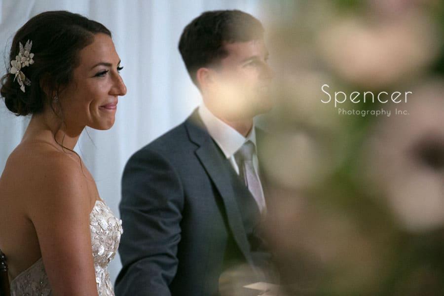 bride watching parents give wedding reception speech