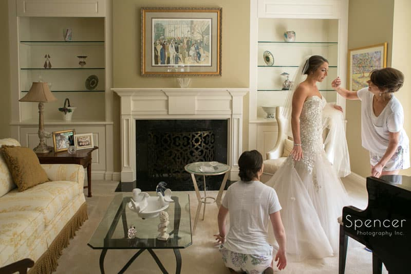 bride and mom putting on liancarlo wedding gown