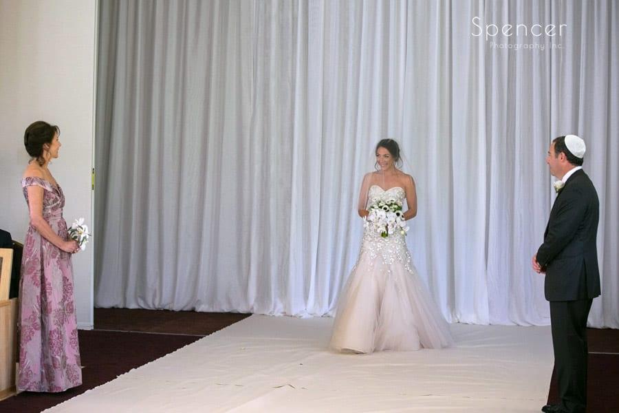 bride walking down wedding aisle at revere road synagogue