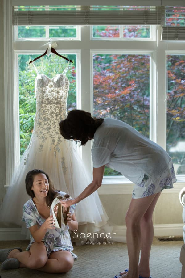 mom handing bride her wedding day shoes