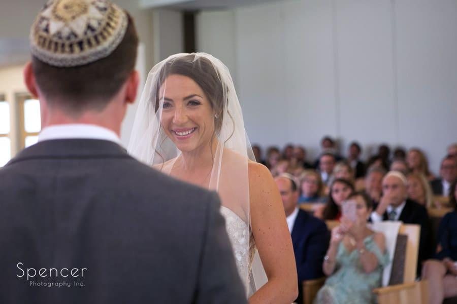 bride smiling at groom at revere road synagogue wedding