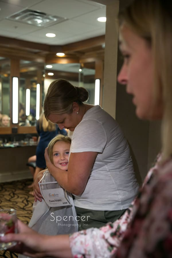 mom hugging flower girl on wedding day at Firestone Country Club