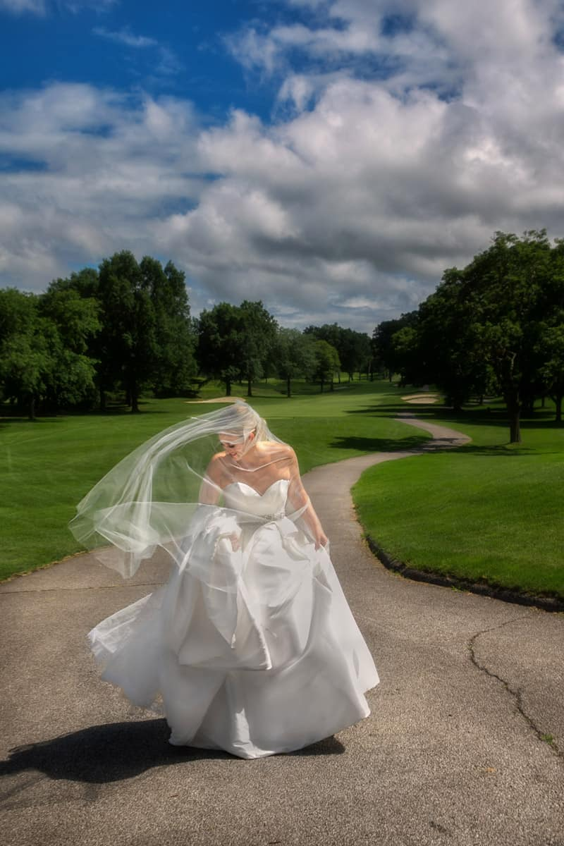 brides wedding dress blowing at Firestone Country Club