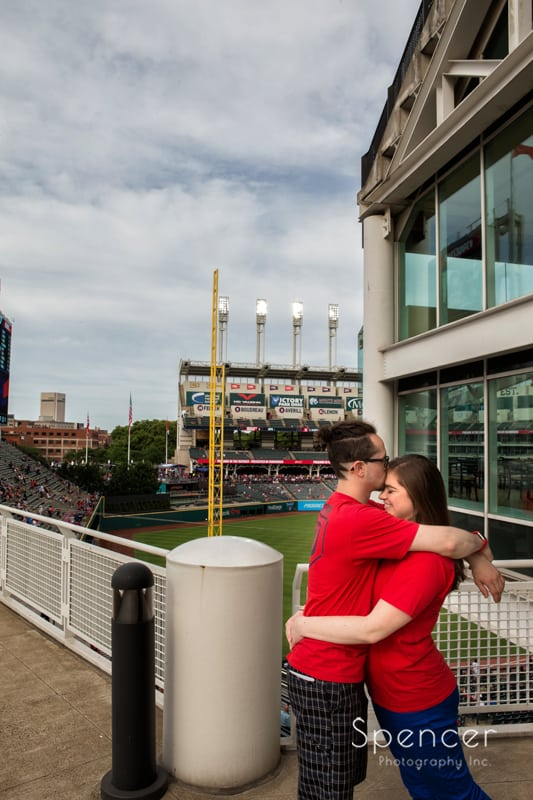 couple hugging during engagement pictures at progressive field