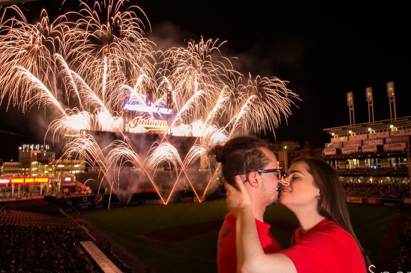 couple kissing during fireworks engagement session at progressive field