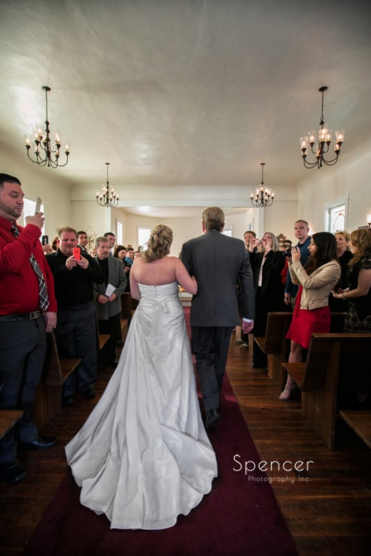 dad walking bride down aisle during wedding ceremony at Frostville Church