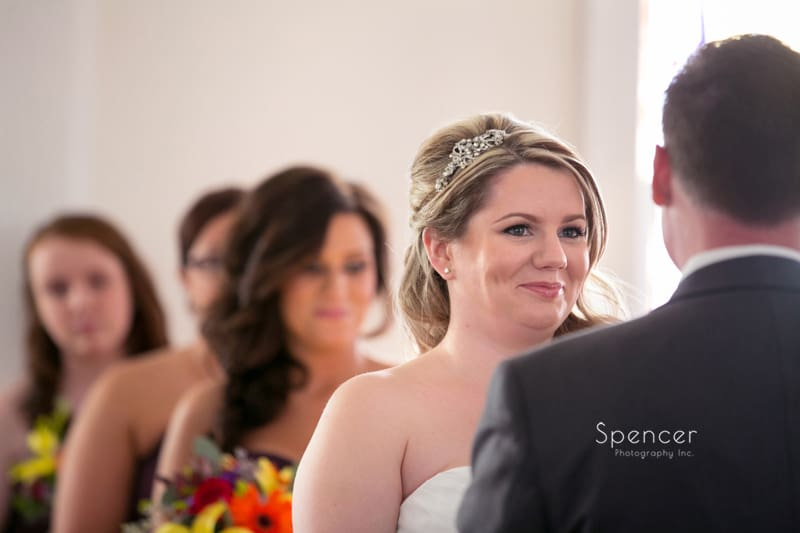 bride smiling at groom during wedding ceremony at Frostville Chruch