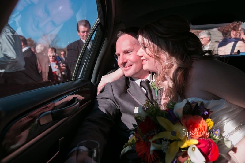bride and groom leave wedding ceremony in limo