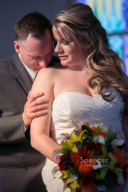 groom kissing bride on wedding day at Frostville Church