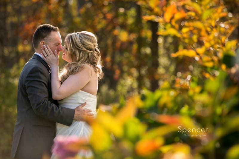 bride gives groom initmate kiss in fall wedding picture