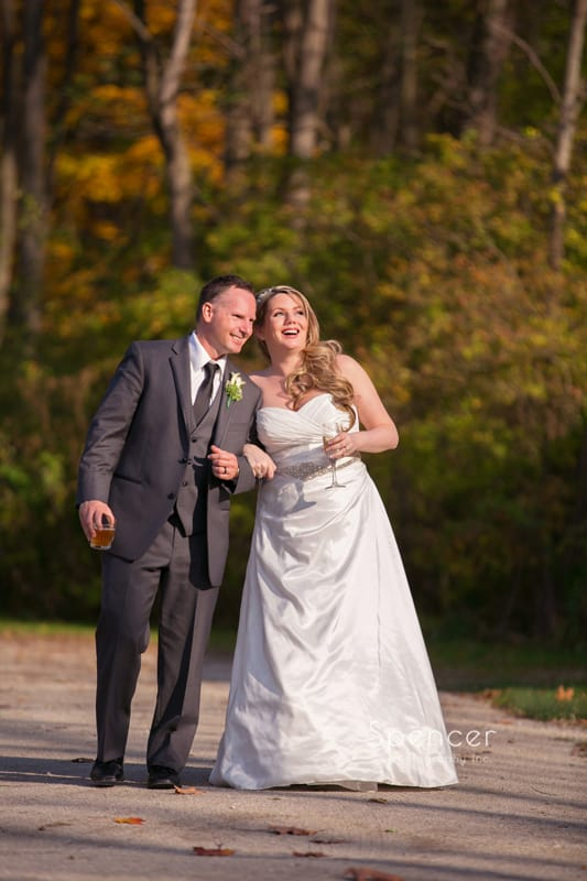 bride and groom walking down pathway for fall wedding picture