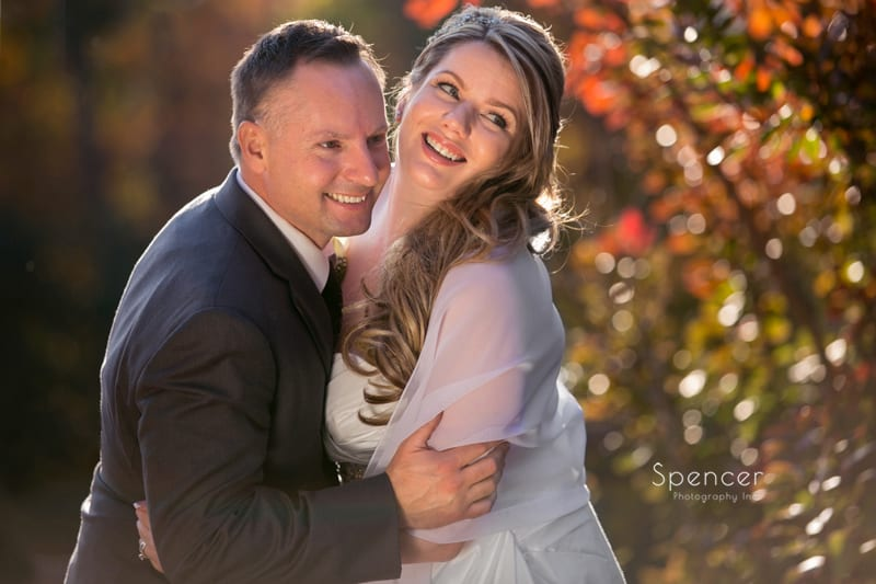 bride and groom smiling for camera in fall wedding picture