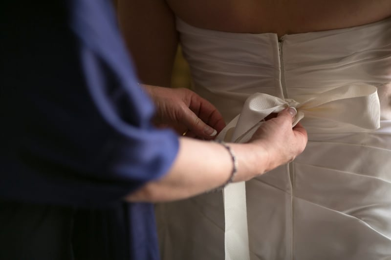 mom tying bow on wedding dress