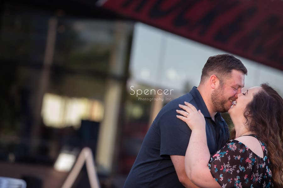couple kissing during engagement session at rock and roll hall of fame