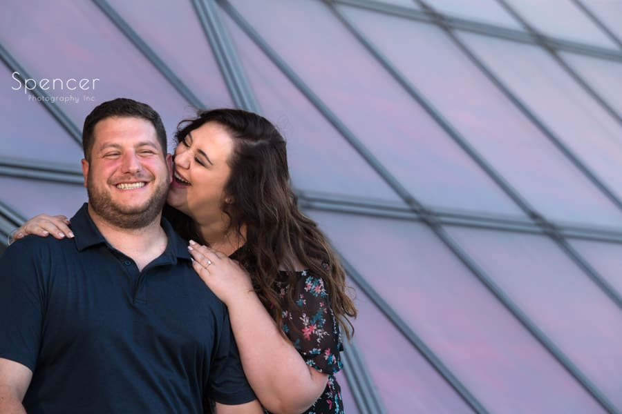 couple laugh during engagement pictures at rock and roll hall of fame