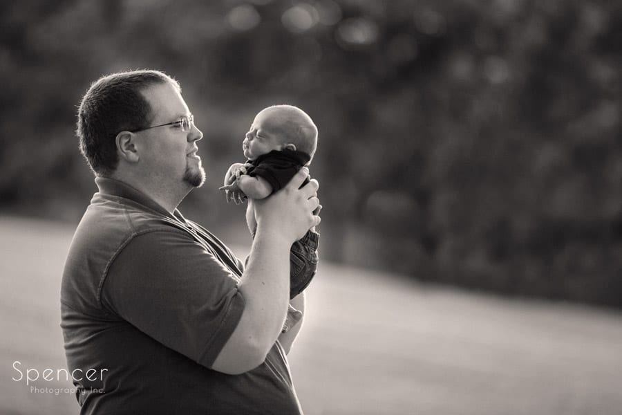 sepia picture of father holding newborn son