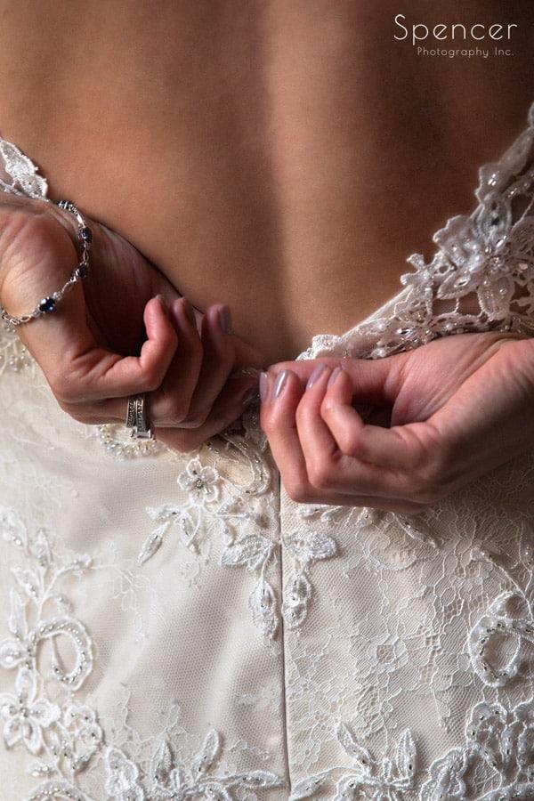 bride zipping wedding dress at Greystone