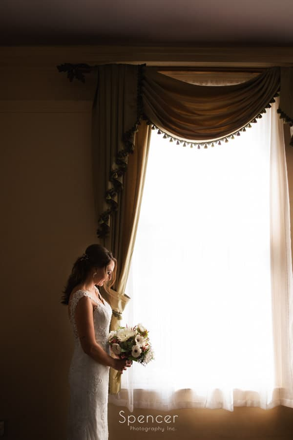 bride holding flowers before wedding at Greystone Hall Akron