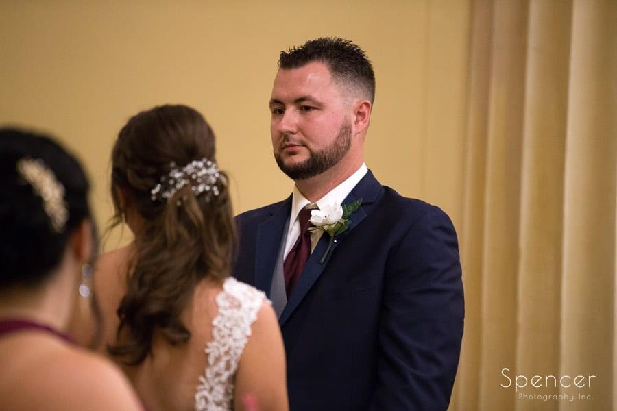 groom looking at bride at wedding altar at Greystone Hall