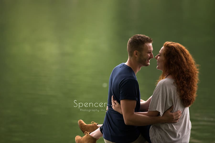 couple laughing at lagoon in engagement pictures at wade oval