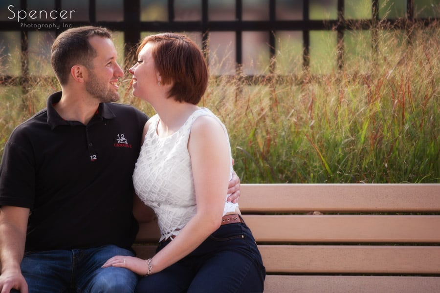 couple sitting on bench for engagement pictures in akron ohio