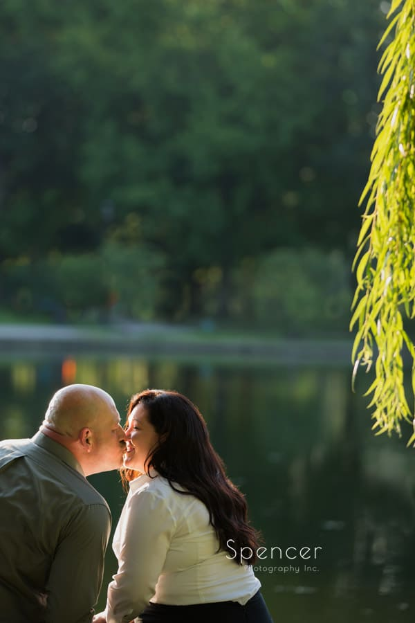 couple smiling for engagement pictures at wade oval park