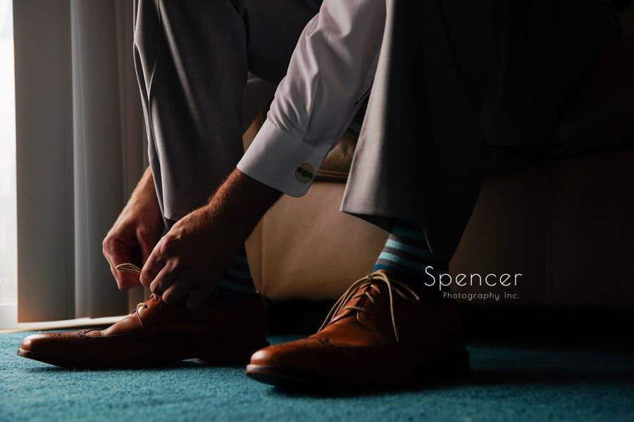 akron groom ties his wedding shoes