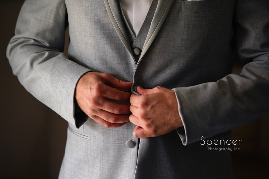 akron groom buttons his wedding jacket