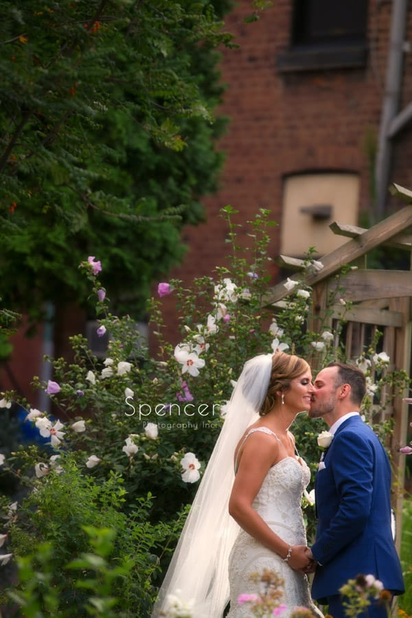 bride and groom kissing in courtyard of Saint Vincent Basilica