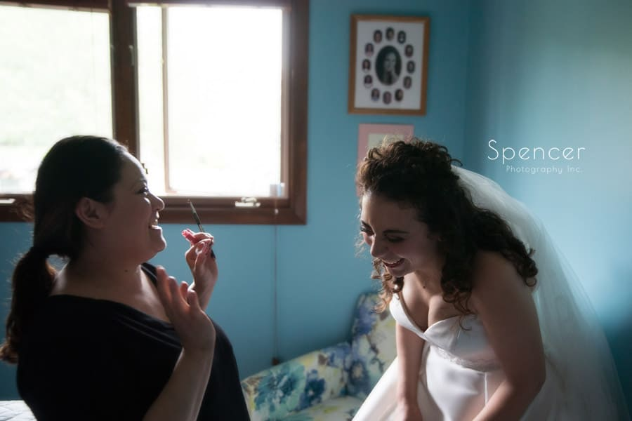 make up artist laughing with bride