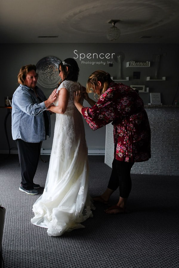 bride getting help with wedding dress in akron ohio