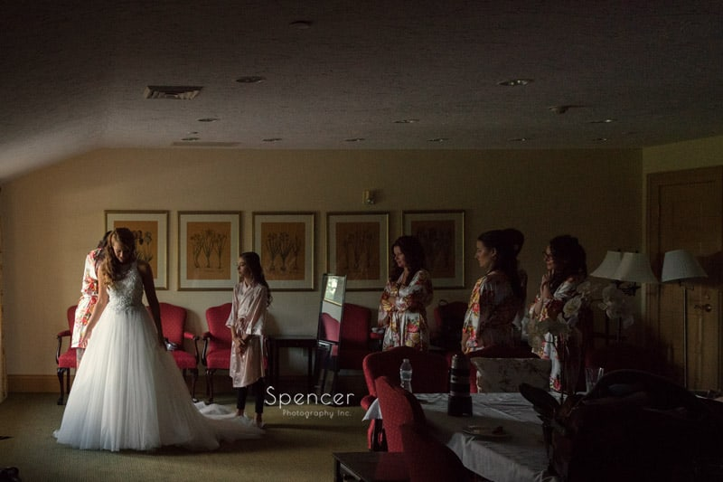 bride putting on her wedding dress at Portage Country Club