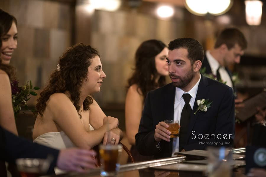 bride talking to groomsman on wedding day at Baxters bar Akron
