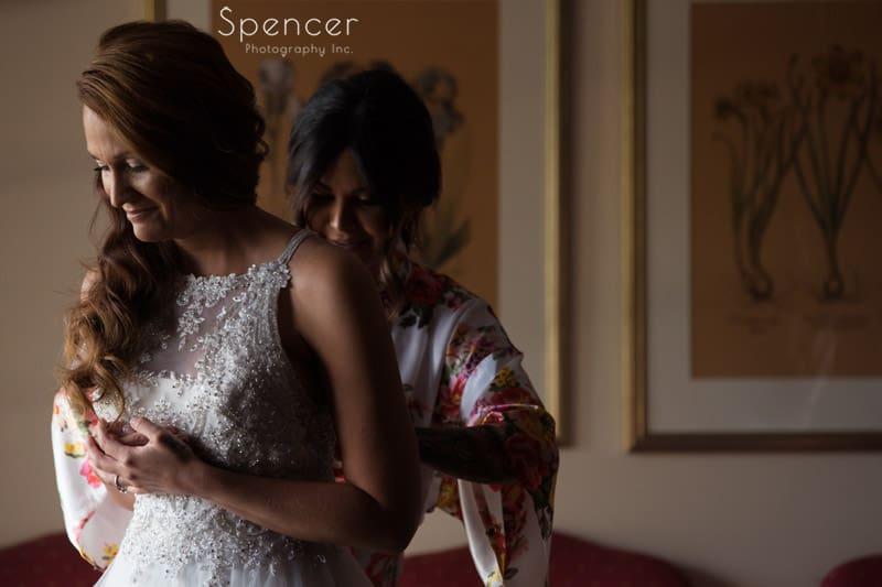 bridesmaid helping bride into wedding dress at Portage Country Club