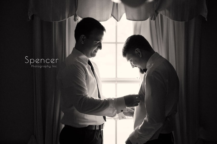best man helps groom get ready for wedding in akron