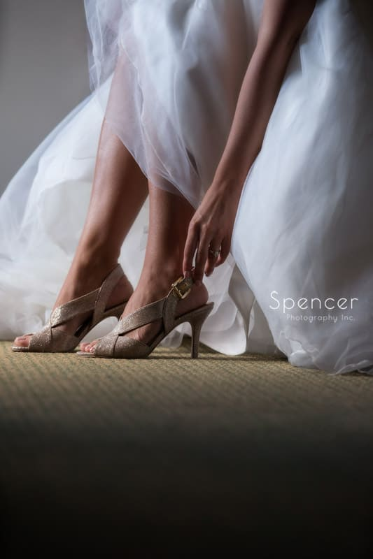 bride adjusting her wedding shoes at Portage Country Club