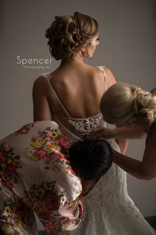 maid of honor and mom helping bride into wedding dress