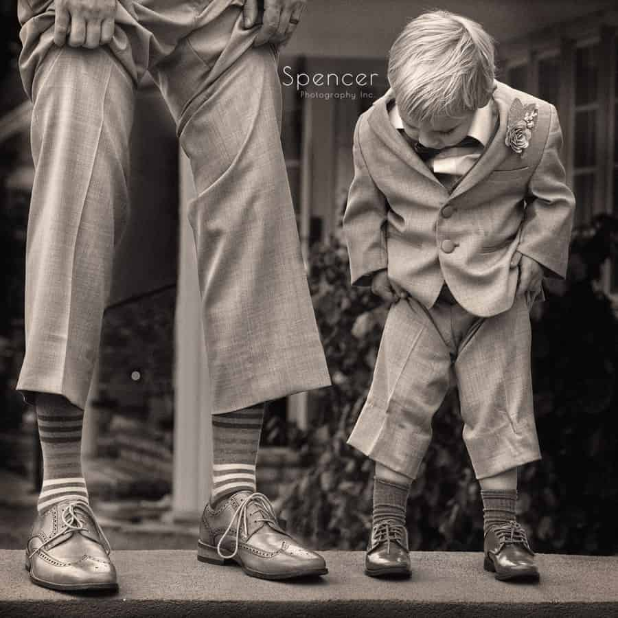 ring bearer and groom comparing wedding shoes