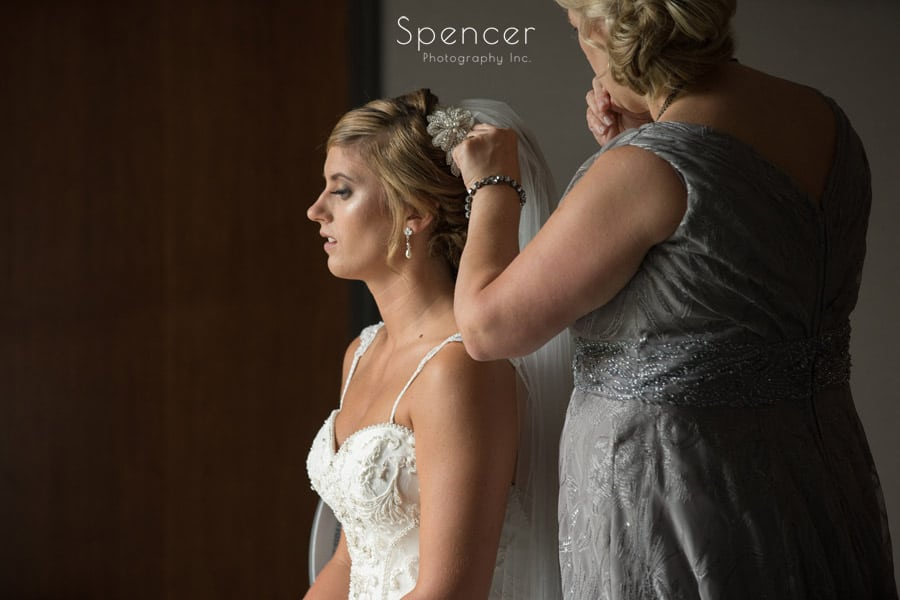 mom helping bride with wedding veil