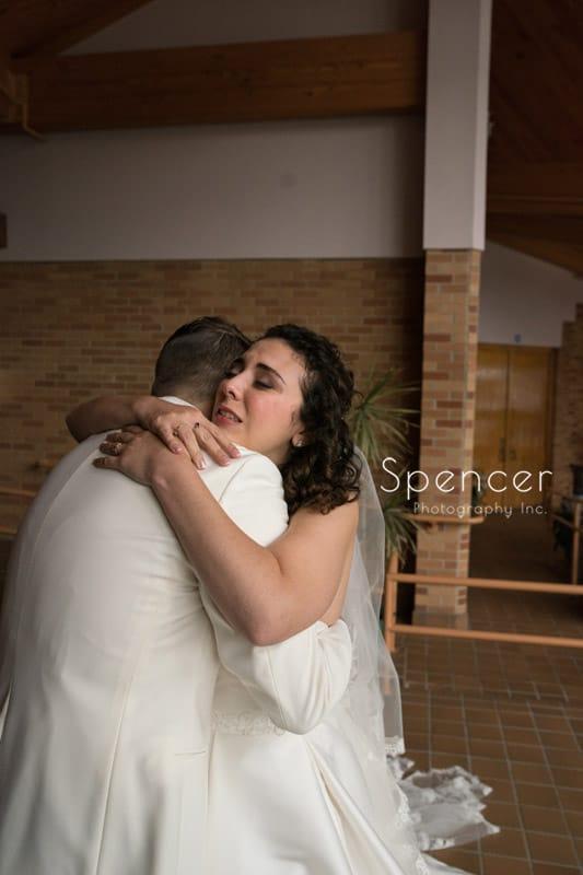 bride hugs groom before wedding ceremony in Akron ohio
