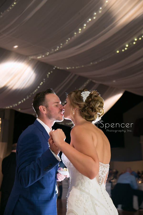bride and groom kiss after cutting cake at Antonelli Event Center