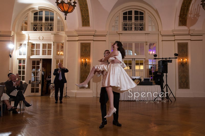 groom twirls bride during first dance at Greystone Hall Akron