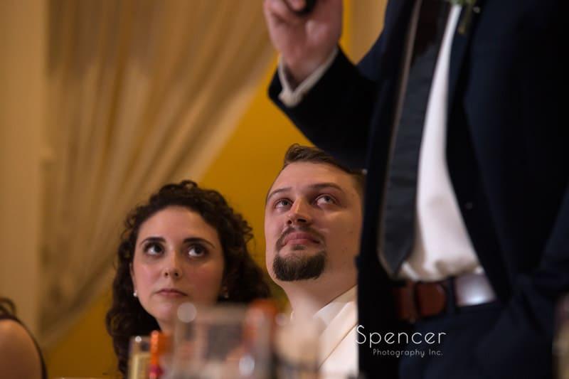 groom listens to best man speech at Greystone Hall wedding reception