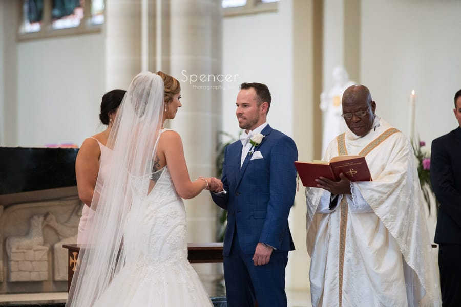 groom looking at bride during wedding ceremony at St. Vincent Basilica